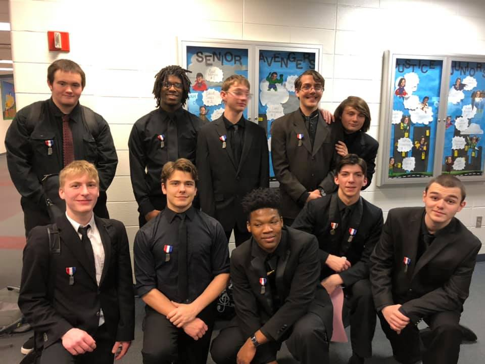 group of male students in all black with small medals at school